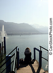 Annecy lake and mountains - Woman resting in front of Annecy...