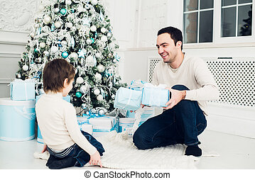 Father and son unwrapping a present lying on the floor.
