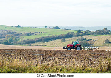 Tractor Ploughing Field - Red tractor ploughing a field on...