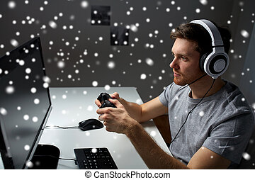 man in headset playing computer video game at home -...