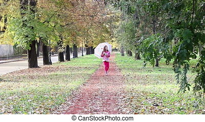 little girl with umbrella walking in park autumn season