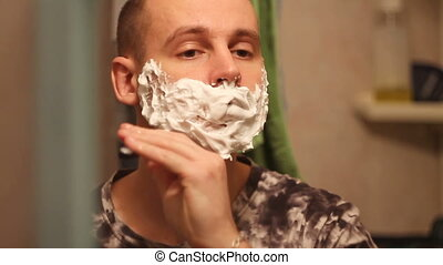 man shaves in the morning in the bathroom