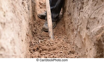 Digging a trench with a spade with feet of man