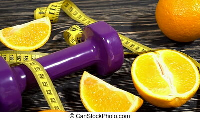 Oranges, juice, dumbbells and measuring tape on wooden...