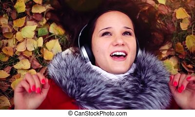 Beautiful happy young woman with headphones lying on autumn...