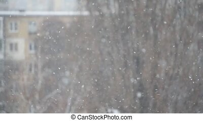 Snow falling in city on blurred background of an apartment...