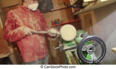 Foot operated spring pole wood lathe.Man operating a foot...