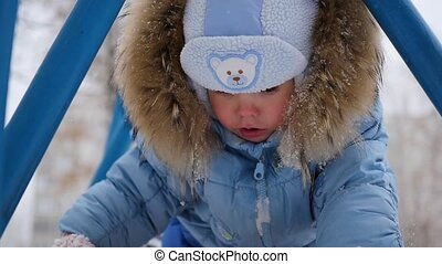 a small happy child plays on the Playground in winter - a...