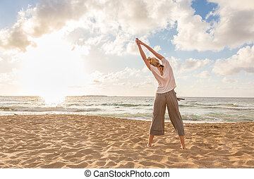 Woman practicing yoga on sea beach at sunset.