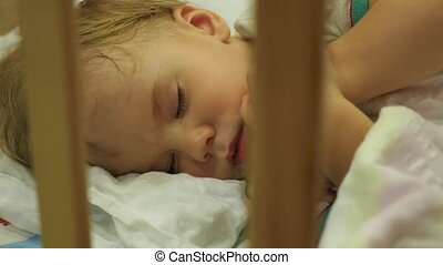 the sweet baby sleeps in a cot and flinches in her sleep