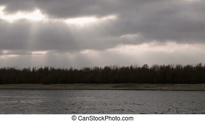 Autumn landscape time lapse. Dark clouds with sun rays fly over tops of forest trees