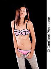 Asian woman in underwear pulling down jeans