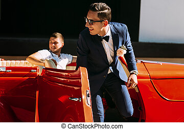 Groom in a suit is going out of the car