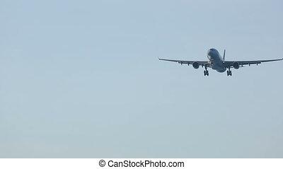 Widebody airplane approaching over ocean before landing in...