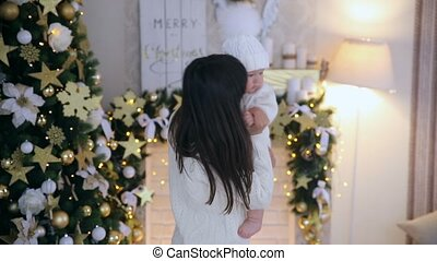 Mother dancing and kissing little son in the christmas studio
