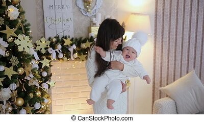 Mother and kissing little son in the christmas studio