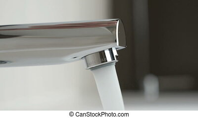 Strong water pressure flowing from a chrome tap - The strong...