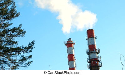 Boiler house chimney. Steam against the clear blue sky. Industrial zone of the city.