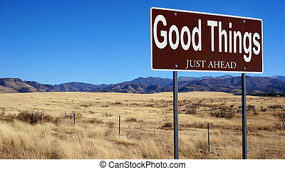 Good Things Just Ahead brown road sign with blue sky and...