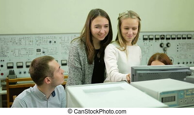 Young student engineers team work in the University of the electrical laboratory. They counsel and test oscilloscope voltmeter readings on the instruments. Future scientists