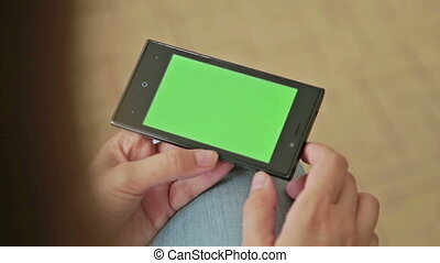 Pretty woman holding in hand smart phone with green screen display