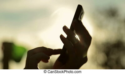 Silhouette of woman's hands with smart phone at sunset