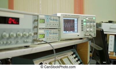Equipment for measuring electrical signals is in the physical laboratory. The scoreboard lit instrumentation data. Oscilloscope and a pulse generator working together.