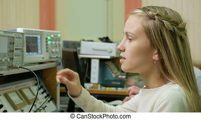 Young woman engineer student working in the lab with electric instrumentation. She carefully turns the wheel clock and looking for indications