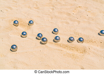 Bocce balls on white sandy beach . - Bocce balls on white...