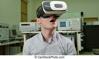 Young male student with glasses of virtual reality in the physical laboratory of the University. Man sees 3D model rotating head. future learning concept