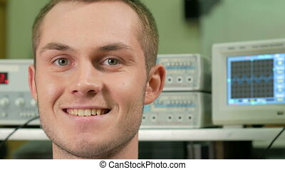 Young attractive man in the room with electrical equipment smiling at the camera. Against the background of a graph on the oscilloscope. The concept of a happy scientist