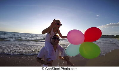 Father and daughter with balloons playing on the beach at the sunset time.