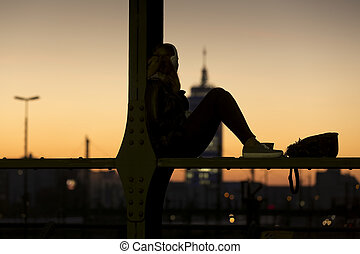 Young woman listening to music at sunset