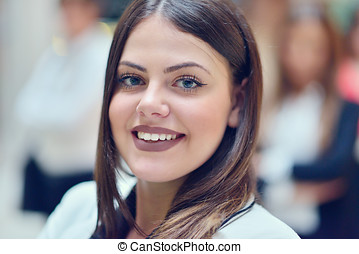 Cute businesswoman in an office with colleagues at the background