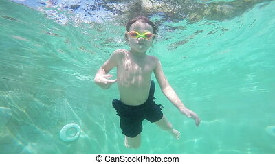 Happy active underwater child swimming in pool at the day...