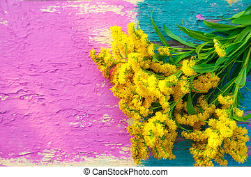 Yellow meadow flowers on colorful bench