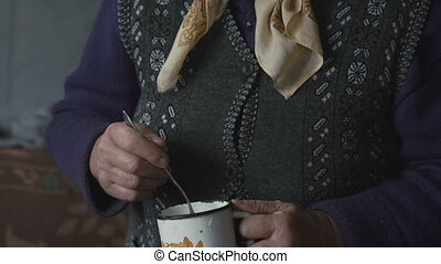 Old grandmother making food using metal mug in full HD