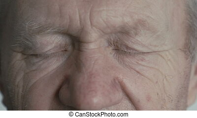 Close up look at camera of old wrinkled handsome man in full...