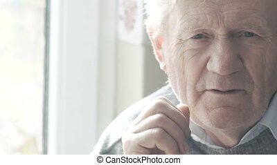 Portrait of emotional happy old man smiling at camera in...