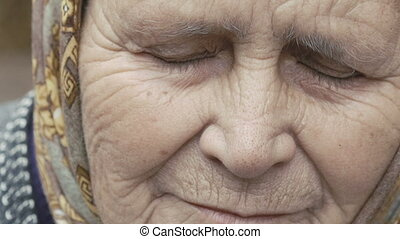 Portrait of old wrinkled tired alone grandmother looking at camera