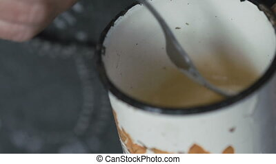 Close up old woman's ill hands churning eggs in metal mug in...