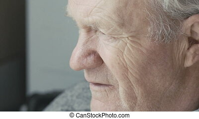 Old grandfather looking at the window