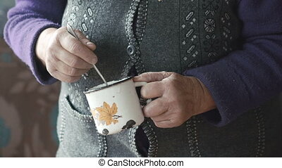 Old woman's shaked hands stiring liquid in the metal mug in...