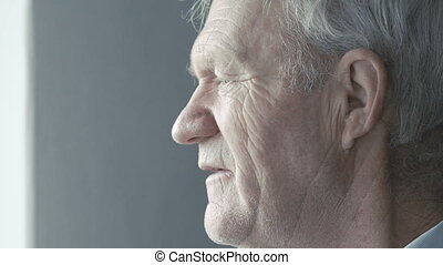 Old grandfather looking at the window and smiling at camera