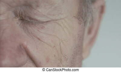 Close up of open blue eye of old man looking at camera on background