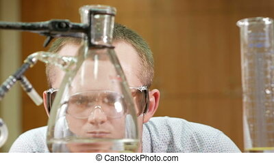 Young student man working with chemicals and writes the...