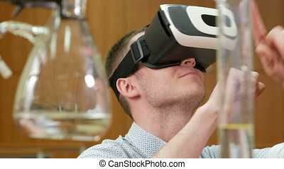 Young male student with glasses of virtual reality in the chemical laboratory of the University. Man sees 3D model rotating head. future learning concept