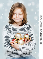girl with Christmas bulbs - cute young smiling girl with...
