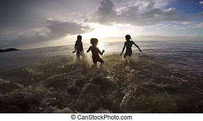 Happy children playing on the beach at the sunset time....