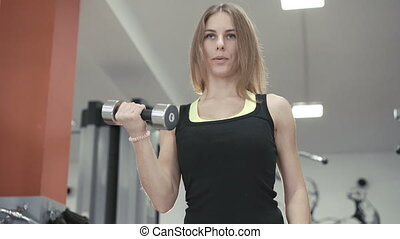 Young girl working out with dumb-bells for biceps in the gym...